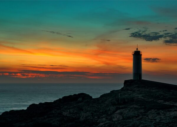 """""""Atlantic Moods #1"""" Artwork is a colour photograph of a lighthouse on the island at the sunset. The photograph carries pastel dark colours. Art print available in different mediums."""