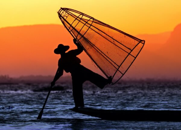 """""""Evening Dance"""" Artwork is a colour photograph of man dancing on the board in the sea holding a net. Art print available in different mediums."""