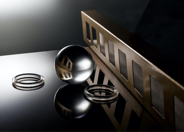"""""""Cardboard and Glass"""" Artwork is a colour photograph of a composition of glass rings, glass ball and metal bulk. It has a dark black and silver colour palette. This artwork is available in different medium."""