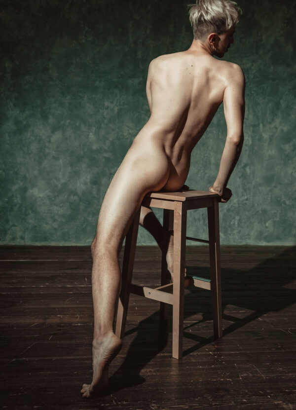 """""""The Silence of Solitude"""" Artwork is a coloured photograph of a nude man facing away from the camera while sitting on a chair in an empty room."""