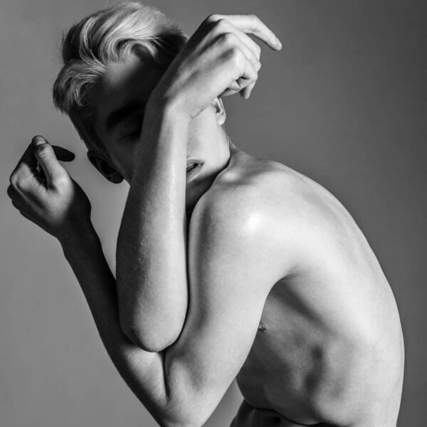"""""""Sensuous #1"""" Artwork is a black and white photograph of a nude man covering himself with his arms."""