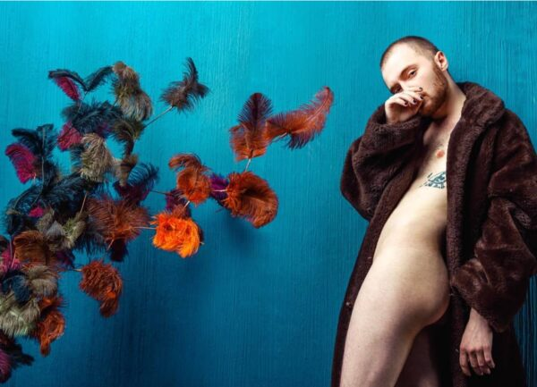 """""""Vaudeville #1"""" Artwork is a coloured photograph of a nude man wearing a coat with coloured feathers."""