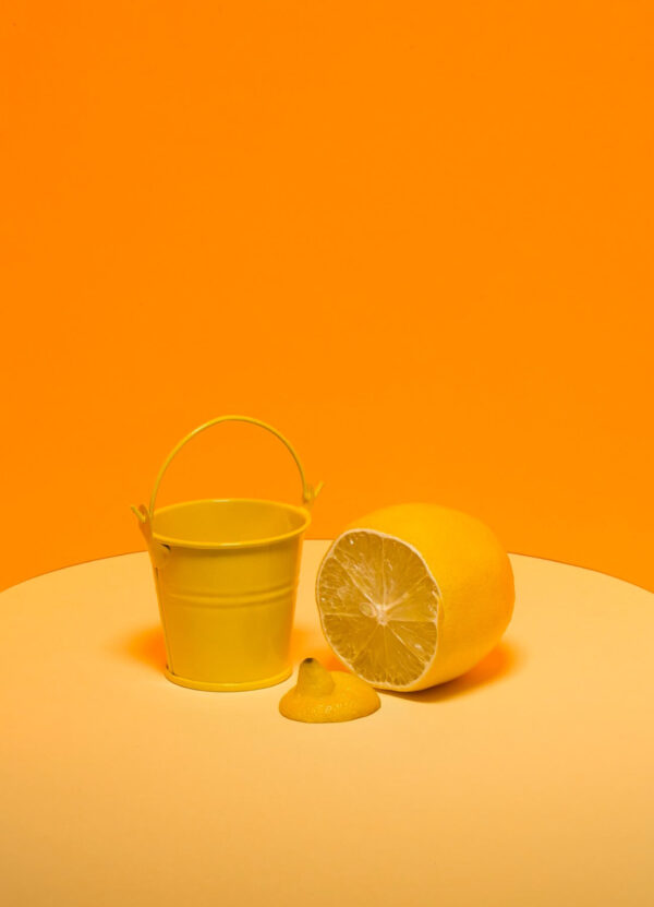 """""""Bucket with Lemon"""" Artwork is an abstract photograph of lemon and a bucket on a bright orange background. Art print available in different mediums and sizes."""