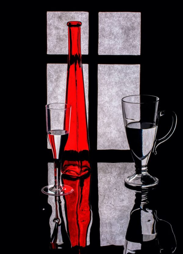 """""""In Front of the Window #1"""" Artwork is a black and white photograph of two glasses and a vase highlighted in red. Art print available in different mediums and sizes."""