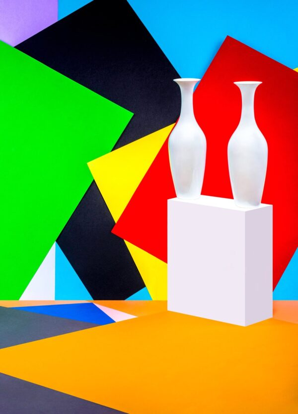 """""""Two Vases"""" Artwork is a photograph of white vases on the bright colourful patchwork background. Art print available in different mediums and sizes."""