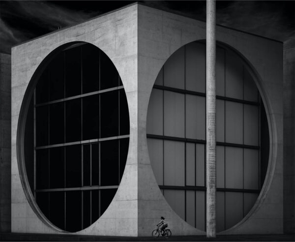 """""""Duality"""" Artwork is a black and white photo of squared building with circular windows and a women on a bicycle riding by."""