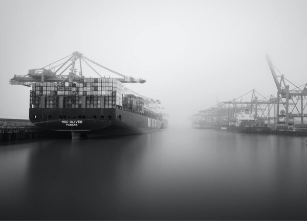 """""""Waltershof bnw II"""" Artwork is a black and white photo taken from the water on cargo ferry in a dock in Hamburg."""