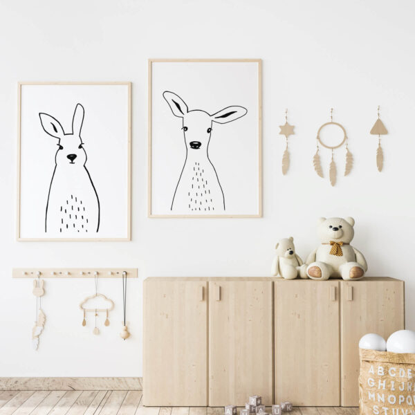 """Paper prints """"Cheeky Rabbit"""" and """"Sweet Deer"""" by Miriam Bischoff framed into light wood shown in the interior (kid's bedroom)."""